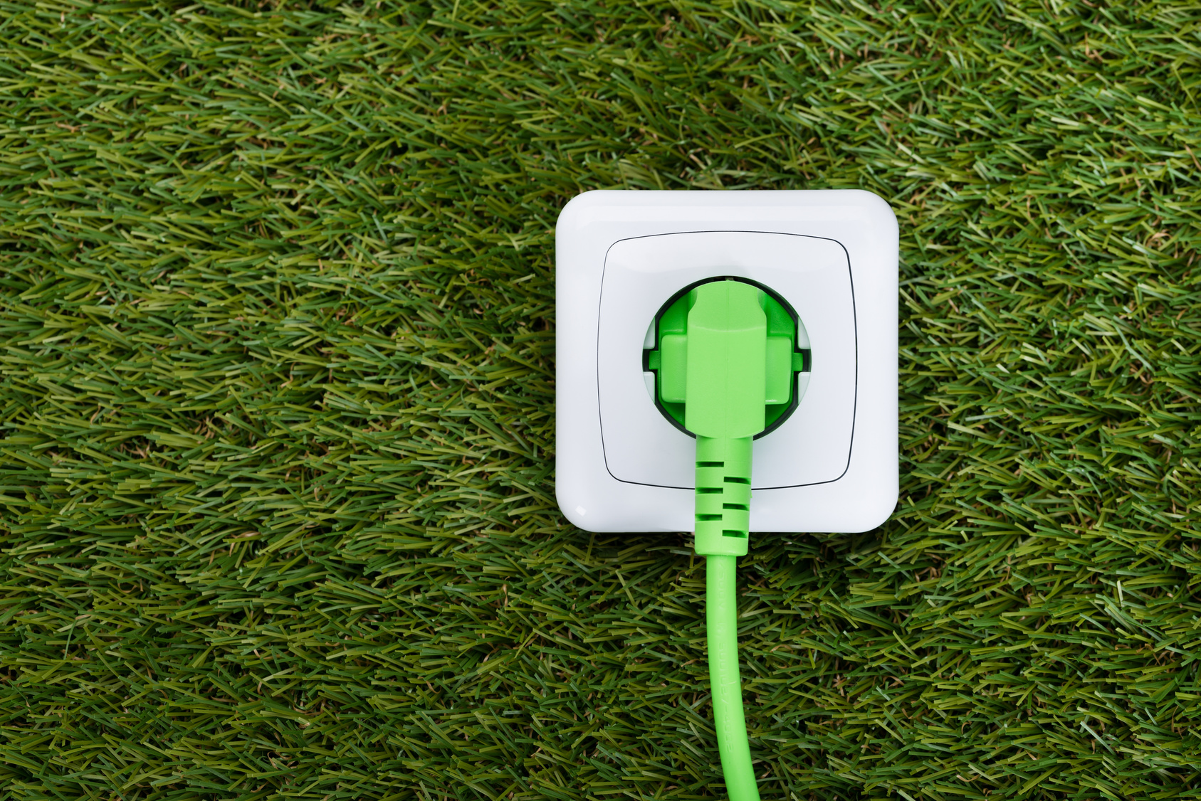 Closeup of green plug in outlet on grass